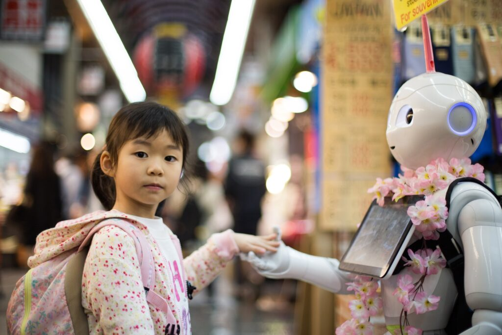 Child looking at photographer while holding the hand of a white robot wearing pink flower garlands.
