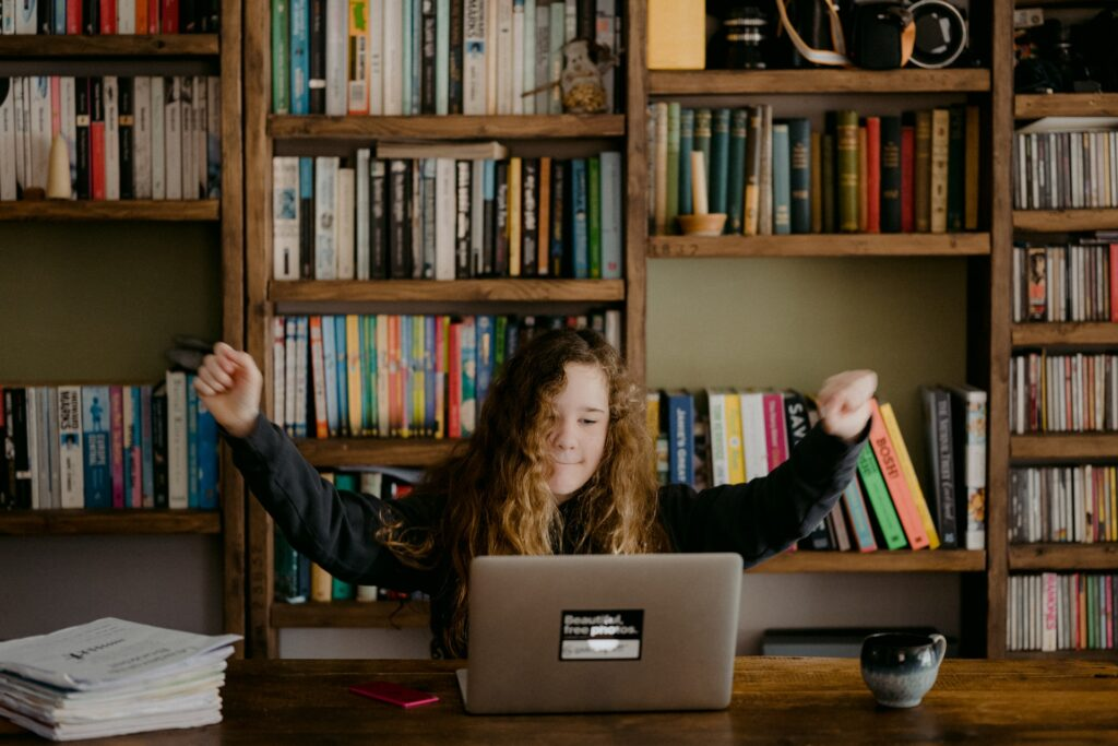 A wall of books is behind a woman sitting in front of a laptop with her arms raised as if in celebration.