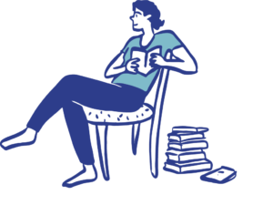 figure sitting in a chair reading, next to a pile of books on the floor.