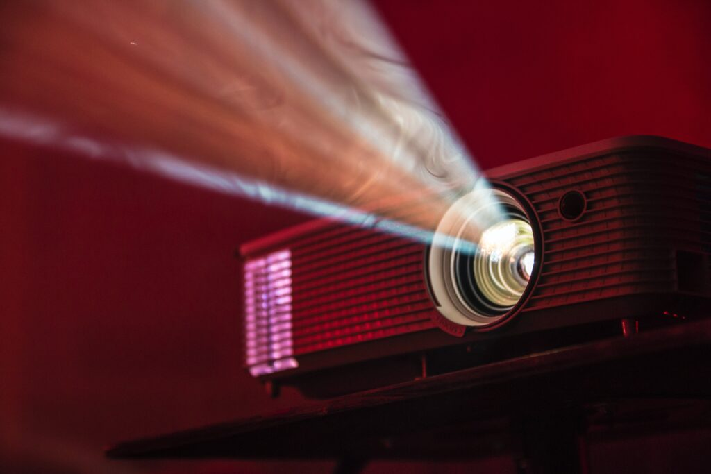 digital projector illuminated beam of light reveals dust and smoke in the air.