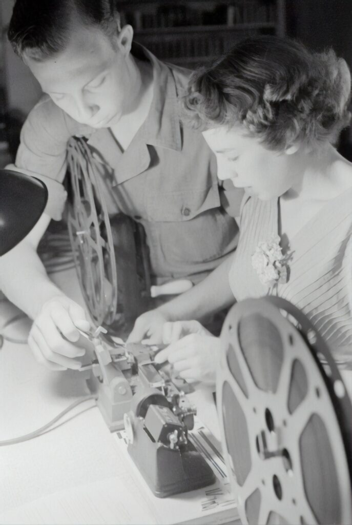 Young man and woman editing film with razor blades and tape.