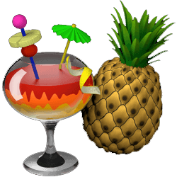 Cocktail with fruit and umbrella garnish next to a pineapple.