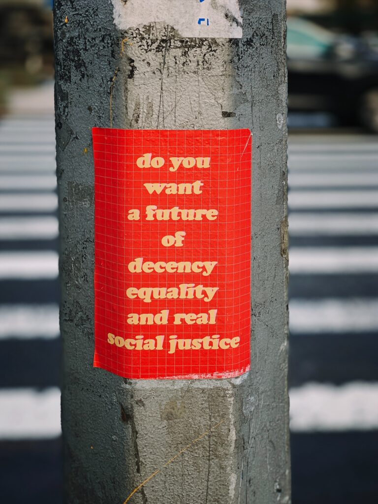 "sign taped to a metal pole, reading ""do you want a future of decency equality and real social justice"""