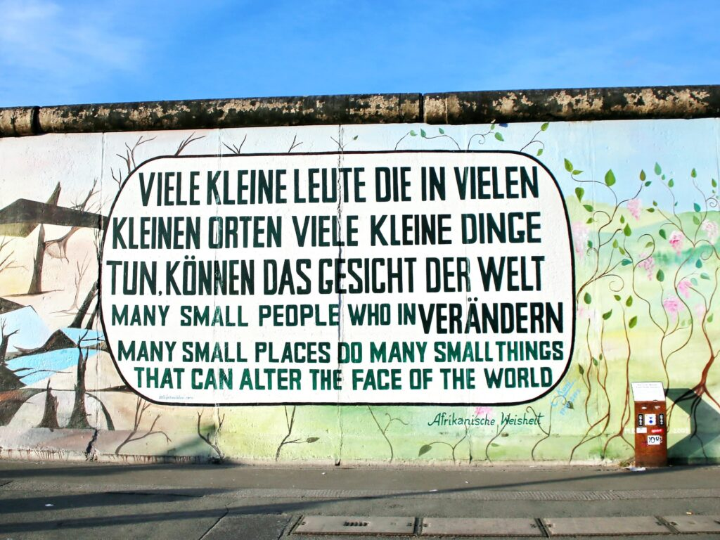 Mural on a wall reads in two languages: Many small people who in many small places do many small things that can alter the face of the world.