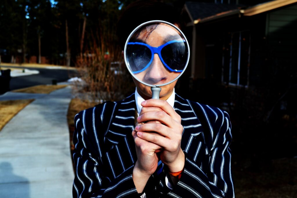 person holding a magnifying glass up to their eyes, which are covered with blue sunglasses.