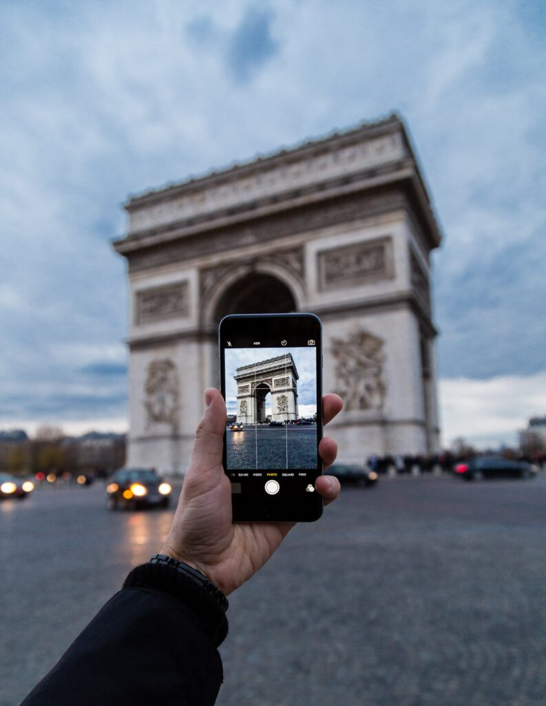 cellphone being held in a single hand, taking a picture.