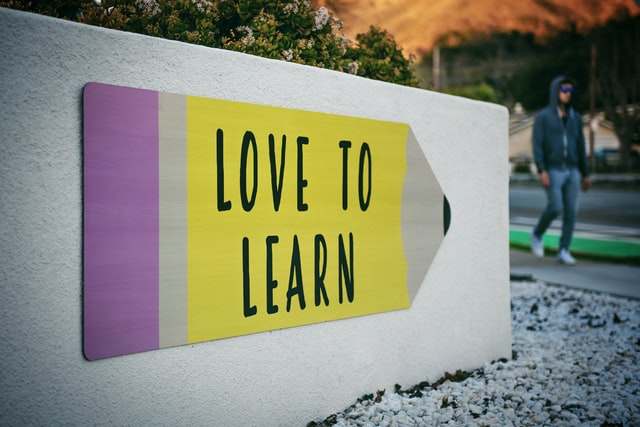 Love to Learn sign depicted on sign that looks like a giant pencil.