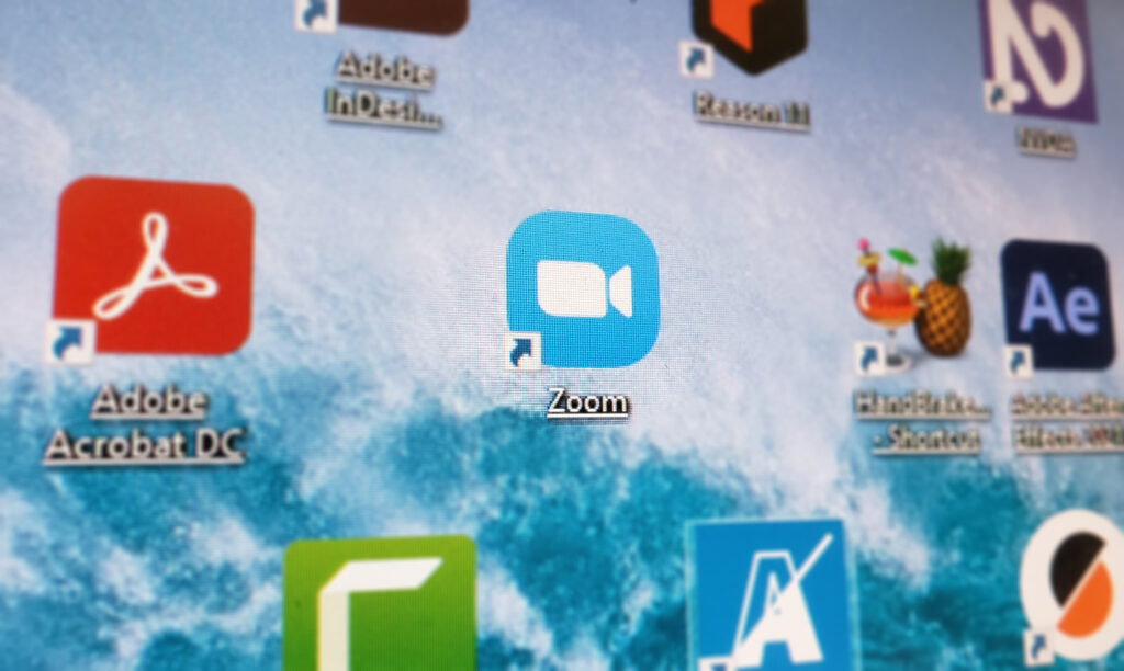 Zoom program icon focused in the midst of a screen of blurred icons for other programs.